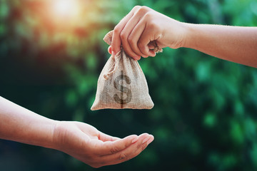 hand giving money bag to another people on green background with sunrise