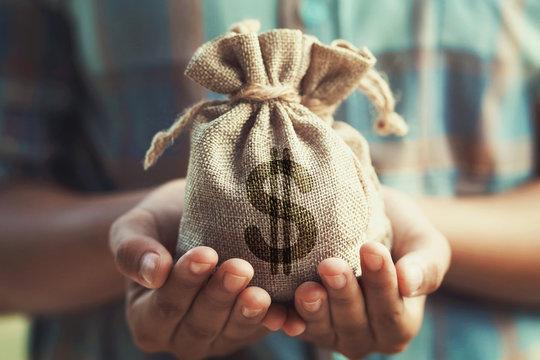 woman hand holding money bag. concept saving finance and accounting