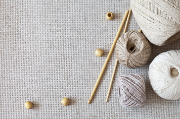 Handicrafts, needlework and hobbies. Wooden crochet hooks and balls of cotton yarn beige color on a canvas background. Тоp view, closeup, flat lay, copy space