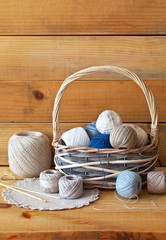 Rustic, retro still life with cotton yarn balls for hand knitting in a wicker basket, handmade napkin and crochet hooks on a wooden background. Handicrafts, needlework and hobbies. Closeup, copy space