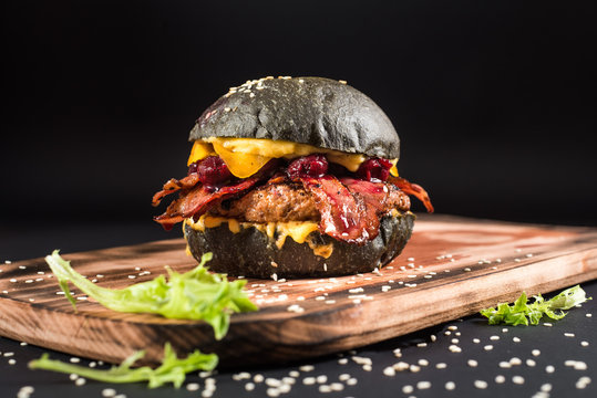 Tasty black burger with meat, bacon, cheese and cherry on the black background