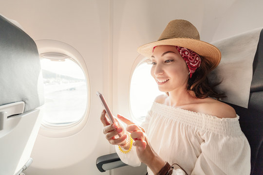 Asian woman passenger sitting in airplane near window and reading news from social networks or using travel applications in smartphone