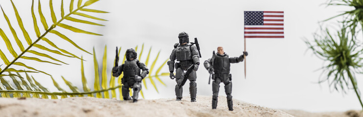 panoramic shot of toy soldiers holding american flag on sand dune Wall mural