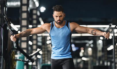 Handsome bodybuilder working out pushing up exercise in gym