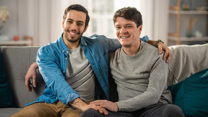 Cute Attractive Male Gay Couple Sit Together on a Sofa at Home. Boyfriend Puts His Hand on Partner's. They are Happy and Smiling. They are Casually Dressed and Their Room Has Modern Interior.