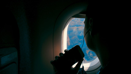 Happiness of asian girl with headphone listening music and taking pictures with smartphone and smiling looking on the airplane window