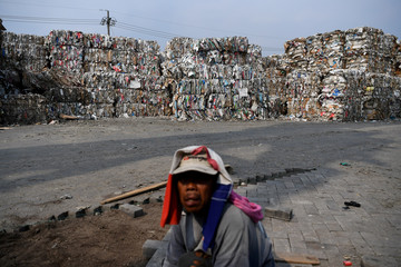 A worker sits near piles of paper waste, imported by a paper factory, in Mojokerto