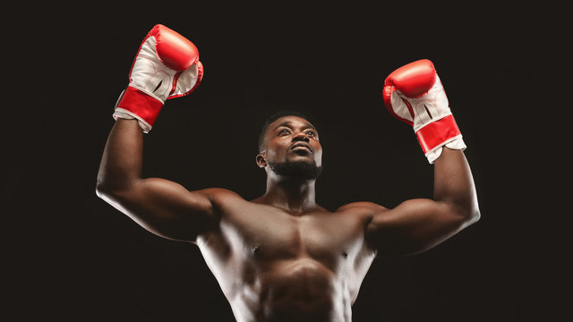 African naked athlete raising hands in boxing gloves
