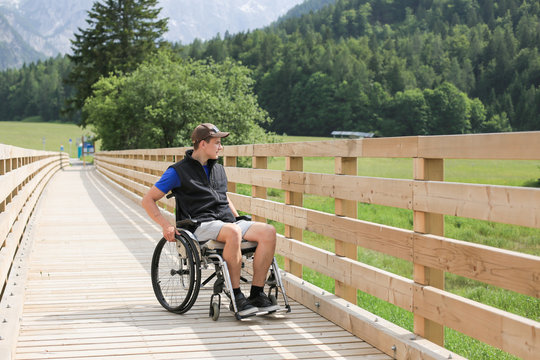 Disabled young man on a wheelchair on a wooden bridge path enjoying in nature looking at beautiful view