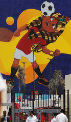 """Police officers walk in front of a picture of Egyptian mascot for the Africa Cup of Nations, named """"TUT"""" at the Cairo International Stadium ahead of the Africa Cup of Nations opening soccer match between Egypt and Zimbabwe in Cairo"""