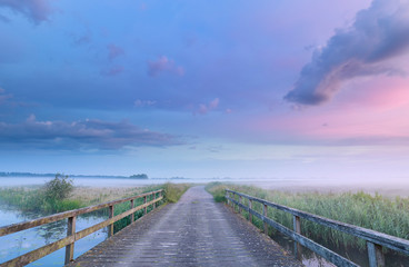 Wall Mural - river bridge in countryside at misty sunrise