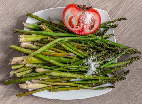 Cooked green asparagus and tomato placed on a plate of food