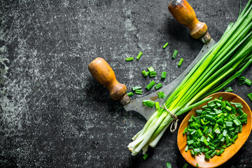 Fototapeta Chopped green onion in a wooden plate with a knife. obraz