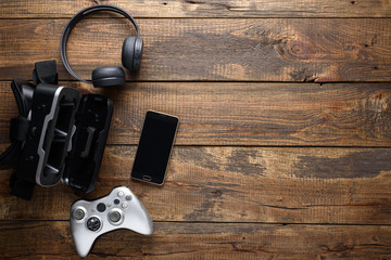 Gamer gadgets. Joystick, VR glasses, wireless headphones, smartphone on wooden textured background with copy space