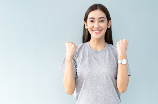 Happy young Asian girl celebrating her success, keeps hands clenched in fists and looking at camera isolated on the gray background