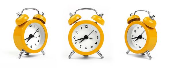 Three yellow alarm clock over white