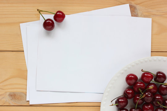 clean sheets of white paper on the table and a plate of cherries, top view