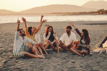 Happy friends sitting on the beach singing and playing guitar during the sunset Wall mural