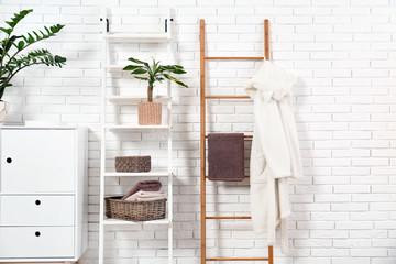 Furniture with clean towels and robe near brick wall in bathroom