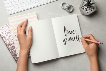 Woman writing LOVE YOURSELF in journal on grey table, flat lay