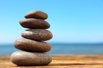 Acrylic Prints Stones in Sand Stack of stones on wooden table against seascape, space for text. Zen concept