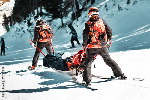 Wall mural Rescuers at a ski resort evacuate the victim from the slope.