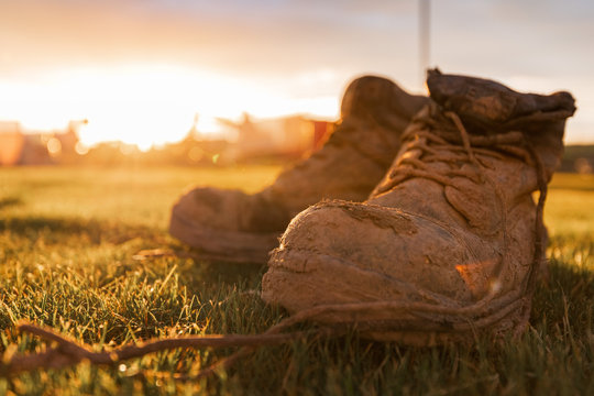 Safety Boots at a construction site covered in mud in front of a bright sunset