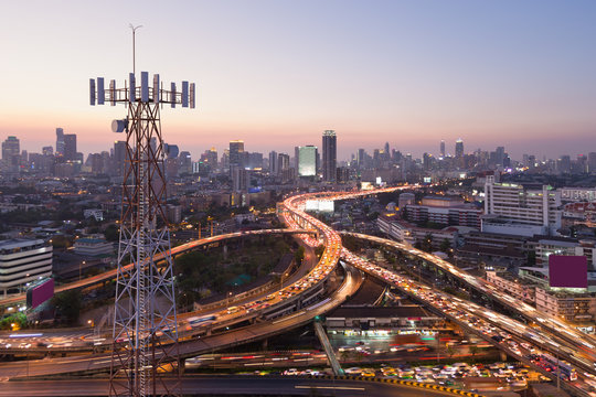 Telecommunication tower with 5G cellular network antenna on city background
