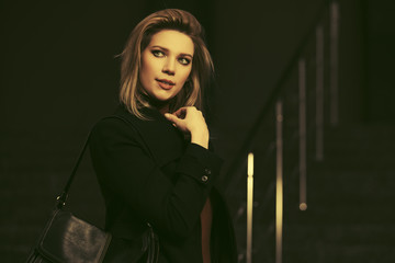 Fashion blonde woman in black coat with leather handbag