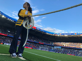 A volunteer holds a rope to pen in photographers during the national anthems of Scotland and Argentina during the Women's World Cup soccer tournament in Paris