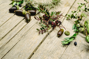 Aged wooden table background decorated with acorns, red berries and dried leaves.