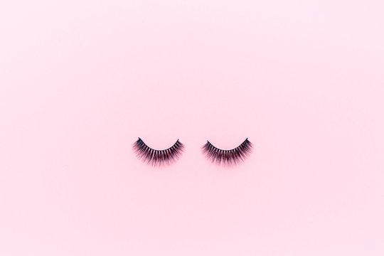 False eyelashes lying on pink background. Beauty and makeup concept. Flatlay, mockup, overhead, top view copy space