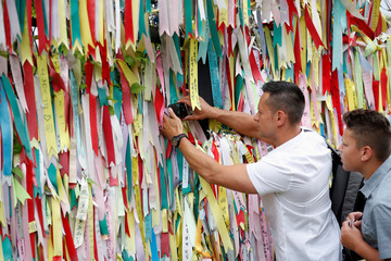 A man tries to take a photograph behind a military fence decorated with ribbons bearing messages wishing for reunification near the demilitarized zone separating the two Koreas in Paju