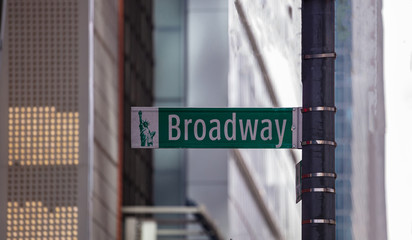 Wall Mural - Broadway road sign. Blur buildings facade background, Manhattan downtown