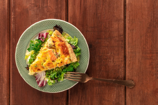 A slice of French quiche with salmon, with green salad leaves, shot from the top on a dark rustic wooden background with copy space