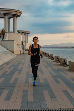 Khabarovsk, Russia - October 07, 2018: a young and attractive girl runs at sunset in a city Park. Healthy fitness woman running outdoors. Amur river in Khabarovsk horizon in the background.