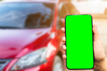 Close-up of female use Hand holding smartphone blurred images touch of Abstract blur of headlight ,window of red car outdoor background.