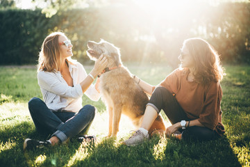 Two girls and dog sitting in the park at the sun set. And enjoying time together