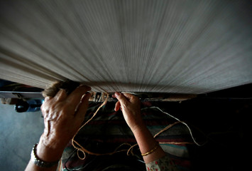 A hand of a Tibetan refugee is pictured as she works to weave a traditional carpet at a Tibetan Refugee Camp in Lalitpur