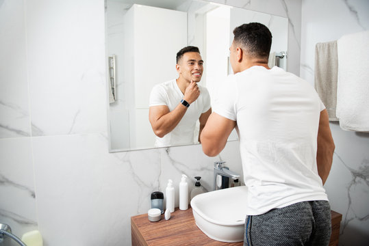 Smiling young man touching his chin before mirror