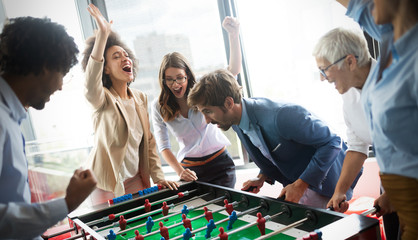 Excited diverse employees enjoying funny activity at work break, creative friendly workers play game