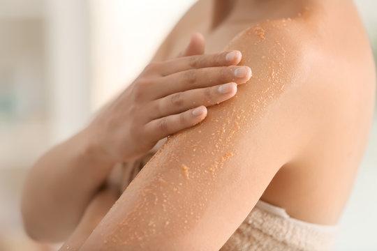 Beautiful young woman applying body scrub at home, closeup