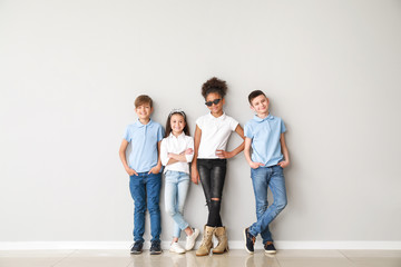 Stylish children in jeans near light wall Wall mural