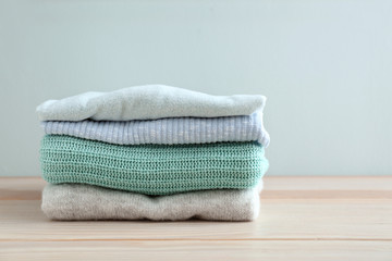 Stack of warm clothes on table against light background
