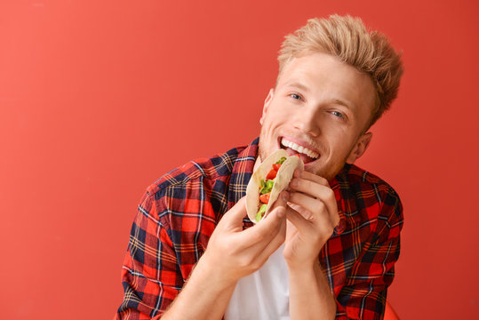 Man eating tasty taco on color background