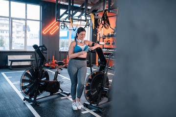 Overweight woman wearing top using her phone in gym