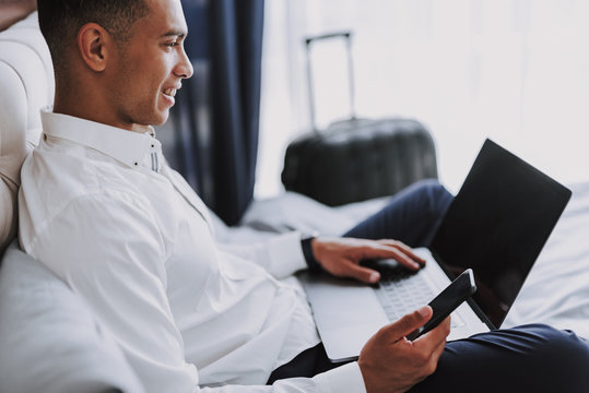Merry young businessman is using gadgets in hotel room