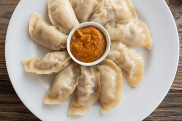 Plate of Nepalese chicken momos and its achar (sauce)