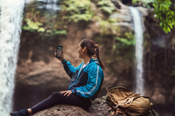 Woman tourists Is shooting a waterfall She is video call with her boyfriend.