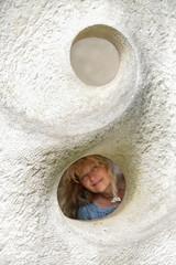 Reife, blonde Frau schaut durch Loch in Sandstein Fassade